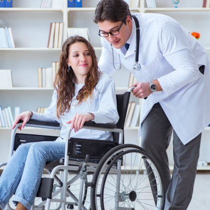 male doctor assisting woman on wheelchair