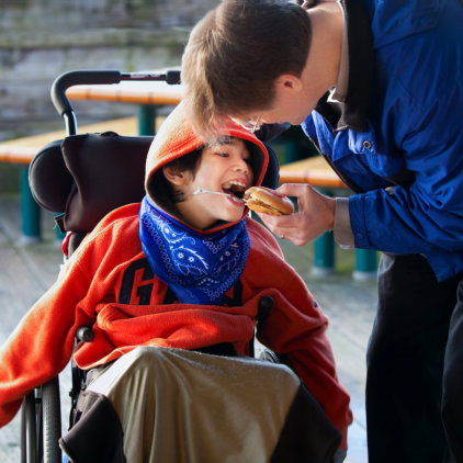 man feeding food to child with disability