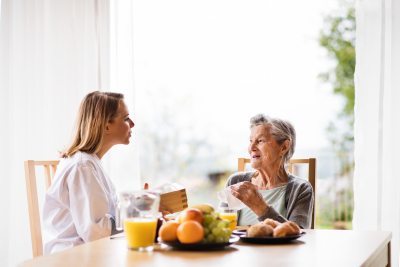 nurse and an elderly woman sitting at the table