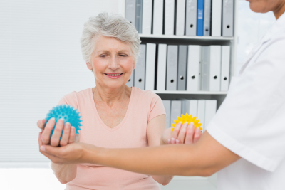 doctor with senior patient using stress buster balls at the medical office