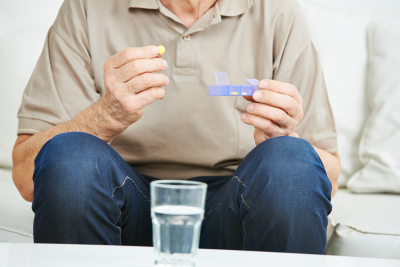 senior man holding medication in his hand